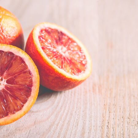 Fresh sliced bloody oranges on a wooden background