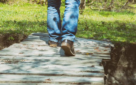 Close-up of male legs in dirt sneakers on a wooden bridge