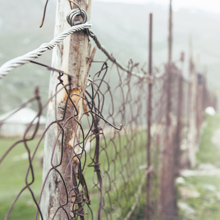 Damaged fence with a grid close-up Stock Photo