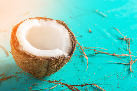 Half of chopped coconut on a blue background with peel Stock Photo