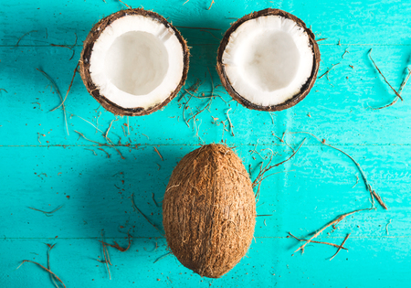 Half and whole coconut on a blue background with peel