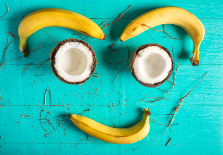 Composition of bananas and chopped halves of coconuts - a smile on a blue background with a peel from coconut