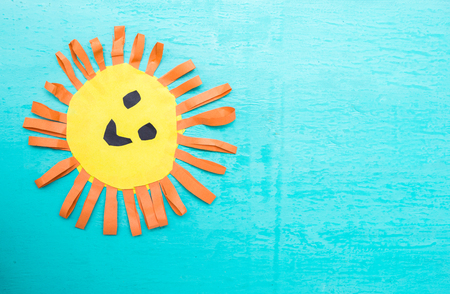 Childrens handmade from colored paper - the sun with a smile on blue background