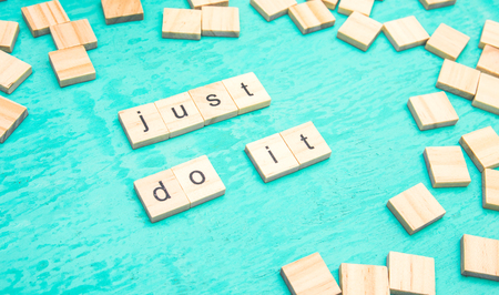 Just do it words laid out with wooden letters of the alphabet concept on a blue background Stock Photo