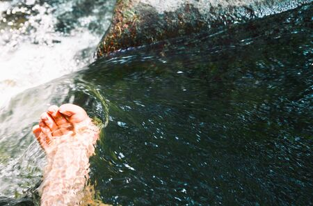 Men feet in a stream of water among the river Standard-Bild