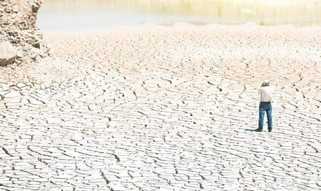Man with a camera at the bottom of a dried lake 스톡 콘텐츠 - 129796300