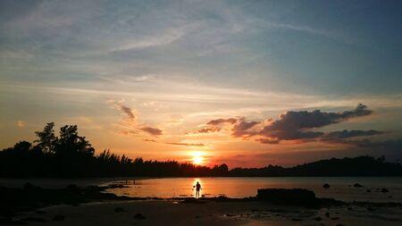 mujer mirando el horizonte: Puesta de sol en la playa Foto de archivo
