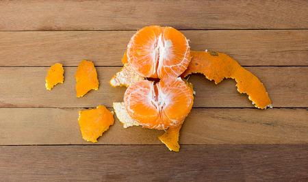 vitamine: Orange being peeled on the wooden floor.