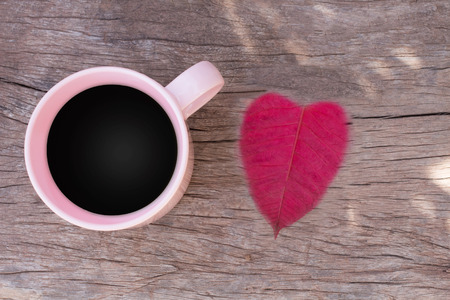 cafe colombiano: Coffee cups with pink top view on the wooden floor and red leaves heart