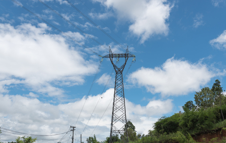wire frame: Electricity pylon silhouetted against blue sky wih cloud background. High voltage tower Stock Photo