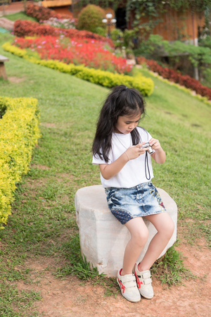 gloaming: Asian girl with a camera in the garden.