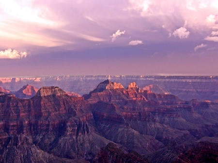 The last pink light of sunset tops the buttes on the North Rim in Grand Canyon, Arizona.