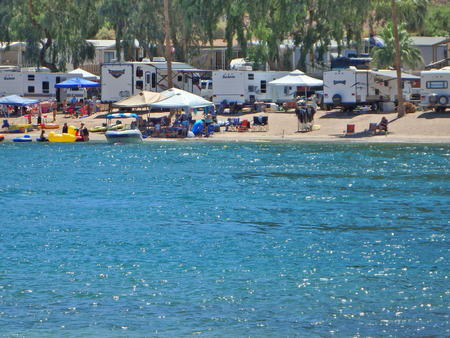 People enjoying the sunshine while picnicking and camping next to the Colorado River in Buckskin Mountain Park south of Lake Havasu City in Arizona.