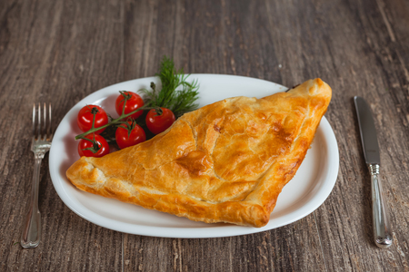 Baked puff on the plate. Steel knife and fork. photo