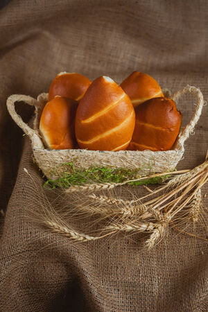 Few buns in a basket. Burlap on the background. photo