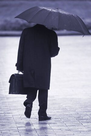 businessman with umbrella walking in the rain photo