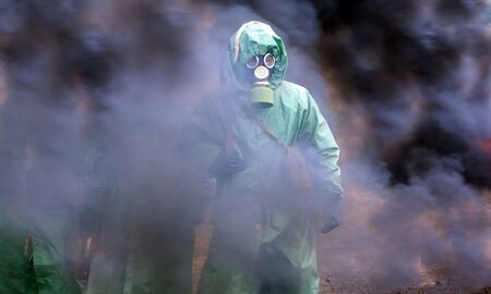 soldiers in chemical protection suites walking through the smoke Stock Photo - 3696720