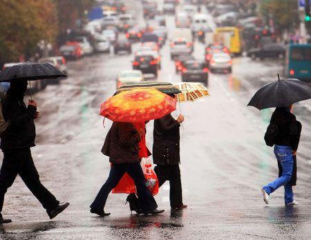 paso de cebra: la población urbana de cruzar la calle en la lluvia Foto de archivo