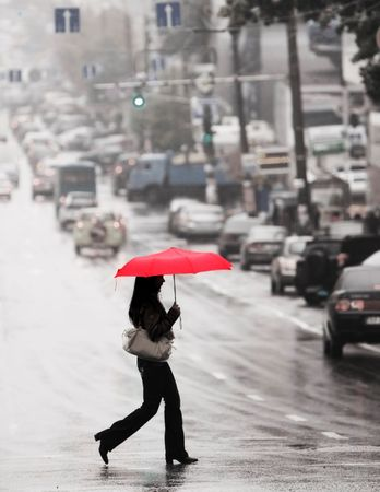 women with red umbrella cross the street in the rain photo