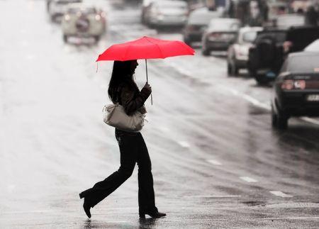 las mujeres con sombrilla roja cruzar la calle bajo la lluvia Foto de archivo - 4587174