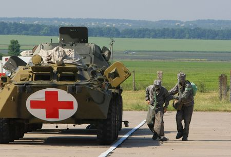 Two soldiers in chemical protection suites run to  armored fighting vehicle Stock Photo - 5111789