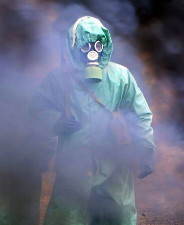 soldiers in chemical protection suites walking through the smoke Stock Photo - 5582350
