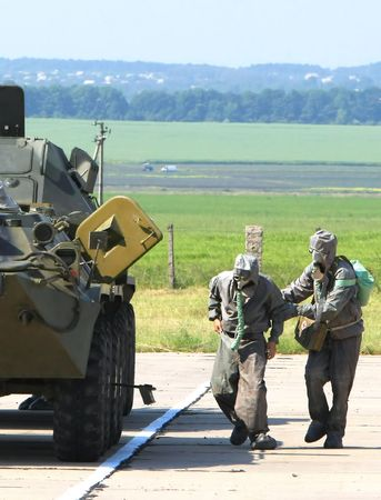 Two soldiers in chemical protection suites run to  armored fighting vehicle Stock Photo - 5639503
