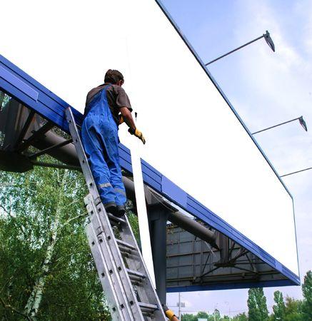 job posting: Media sign worker prepares billboard  to installing new advertisement.