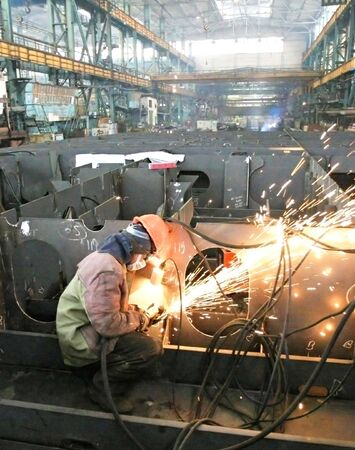 Welder welding a metal part in a dark industrial environment. Stock Photo - 5806605