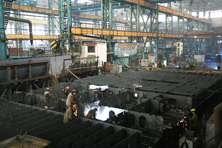 Welders welding a metal part in a dark industrial environment. Stock Photo - 5806618