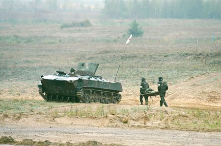 Two soldiers with  hand frame run to armored fighting vehicle Stock Photo - 5891750