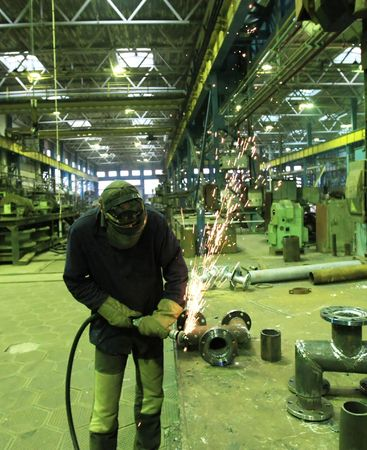 Welder welding a metal part in a dark industrial environment. Stock Photo - 5919888