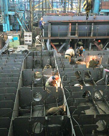 Welders welding a metal part in a dark industrial environment. Stock Photo - 5919893