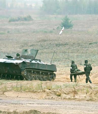 Two soldiers with  hand frame run to armored fighting vehicle Stock Photo - 6028243