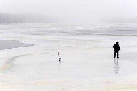 lonely fisherman on frozen river photo
