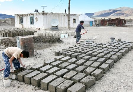 MONGOLIA, AUGUST 06, 2008 -  two  mongolian boys prepare  a brick for construction of house Stock Photo - 6887805