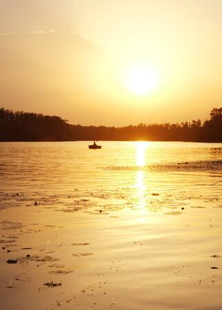 Silhouette of a fisherman on the river at sunset Stock Photo - 7518700
