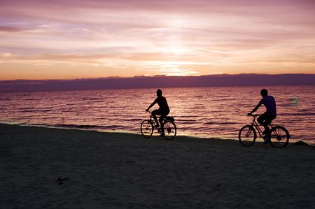 Two people rides by bicycles on the Baltic sea beach photo