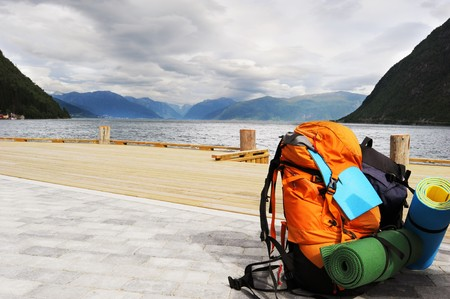 Tourists backpack on a pier in Norwagian fjords