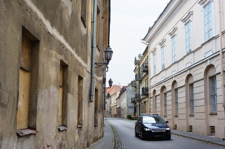 Modern car in narrow paved street of Vilnius old downtown Stock Photo - 8181208