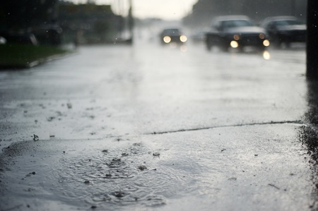 hurricane lamp: Puddle near the wet road in the rain Stock Photo