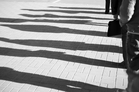 Shadow of a people standing in a queue photo