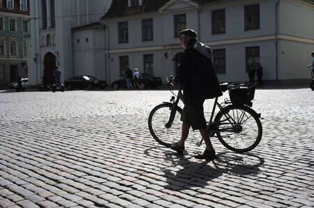 RIGA, LATVIA - AUGUST 9: Man walking his bicycle on an old cobblestone road in Old Town of Riga on August 9, 2010