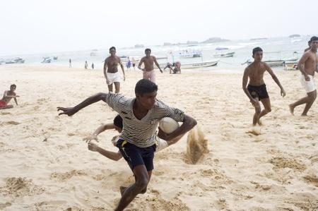 Hikkaduwa, Sri Lanka - 4th, 2011: Young sri lankans plaing football on the beach