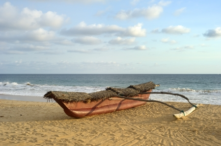 outrigger: Traditional sri lankan fishing boat on ocean beach at sunset