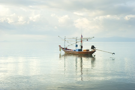 Traditional thailand boat  in the sea at sunrise photo