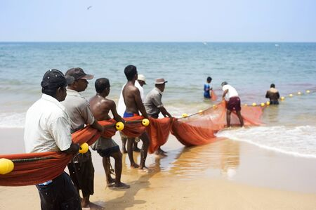 Hikkaduwa, Sri Lanka - Feb 19, 2011: Lokal fishermans pulling net from the ocean. Fishing in Sri Lanka is a tough job but this is the way they earn their living Редакционное
