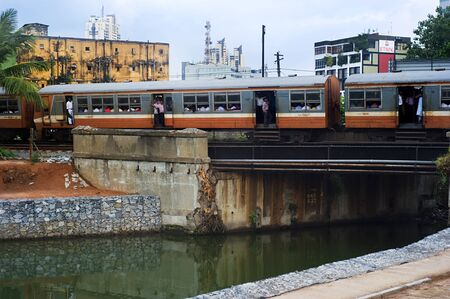 get across: Colombo, Sri Lanka - Feb 22, 2011:  Sri Lankan train passing across the river in Colombo. In Sri Lanka, trains are a cheap, safe and enjoyable way to get around.  Trains link the major cities and have several classes