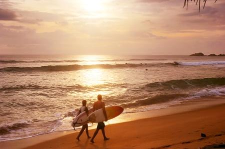 Sri Lanka, Hikkaduwa - March 3, 2011: Couple of surfers walks along the beach in Hikkaduva - is the second best surf paradise in Sri Lanka
