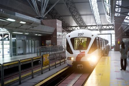 peron: Kuala Lumpur , Malasia - March 16, 2011: Kuala Lumpur LRT train arriving on train station. Kuala Lumpurs metro or rapid transit system consists of 6 metro lines operated by 4 operators. Editorial